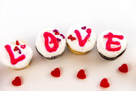 frosting': Valentines Day cupcakes with frosting letters spelling LOVE Stock Photo