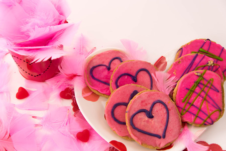 frosting': Valentines Day decorations and cookies with pink frosting and hearts Stock Photo