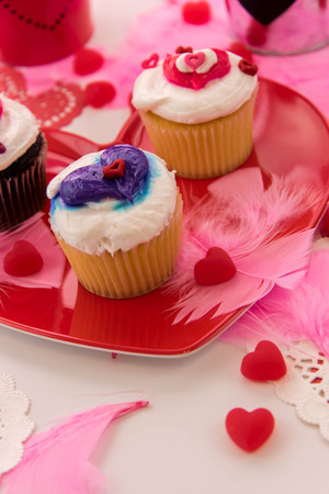frosting': Valentines Day decorations and cupcakes with white frosting and hearts