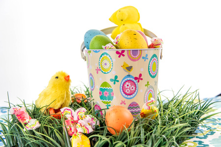 Easter eggs, candy and chicks in bucket on grass