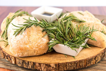 balsamic: a fresh baked loaf of rosemary bread and olive oil and balsamic vinegar