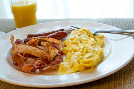 hearty eggs, bacon and sausage breakfast on a plate