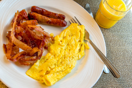 hearty: hearty eggs, bacon and sausage breakfast on a plate