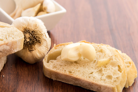 carbs: a fresh baked loaf of bread with whole cloves of roasted garlic