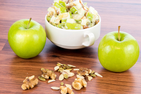 condensed: healthy snack: apple salad with almonds, walnuts and pumpkin seeds, condensed milk and lemon juice