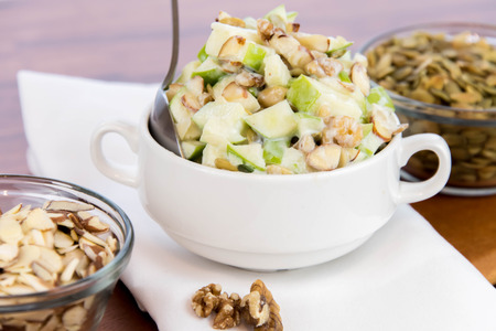 healthy snack: apple salad with almonds, walnuts and pumpkin seeds, condensed milk and lemon juice