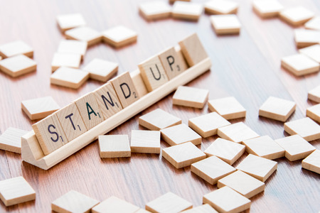and spelling: April 4, 2015:  Houston, TX, USA - Scrabble Word Game wood tiles spelling Stand Up