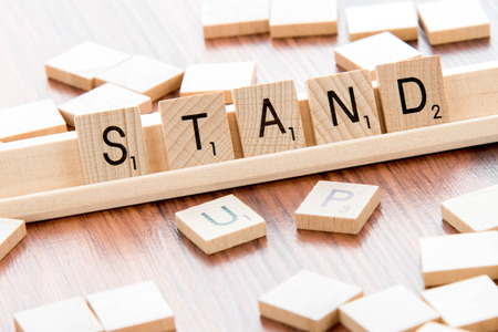 word game: April 4, 2015:  Houston, TX, USA - Scrabble Word Game wood tiles spelling Stand Up