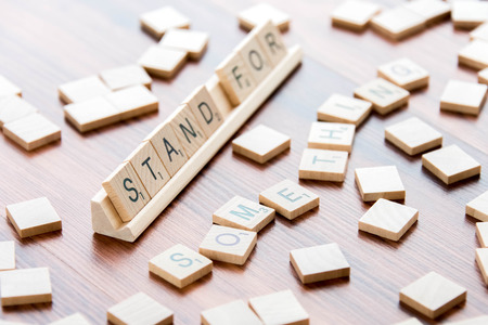word game: April 4, 2015:  Houston, TX, USA - Scrabble Word Game wood tiles spelling Stand For Something