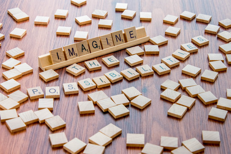 tx: April 4, 2015:  Houston, TX, USA - Scrabble Word Game wood tiles spelling Imagine The Possibilities