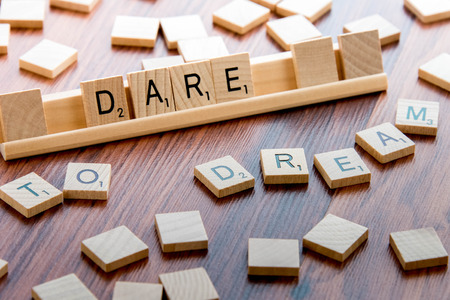 April 4, 2015:  Houston, TX, USA - Scrabble Word Game wood tiles spelling DARE TO DREAM Stock Photo - 39009362