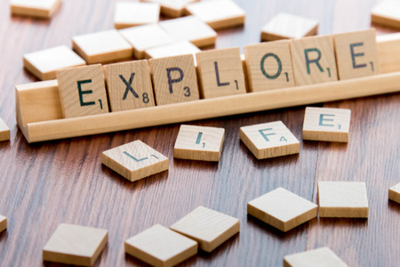 and spelling: April 4, 2015:  Houston, TX, USA - Scrabble Word Game wood tiles spelling EXPLORE LIFE