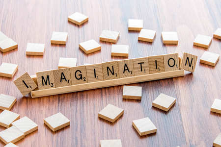 and spelling: April 4, 2015:  Houston, TX, USA - Scrabble Word Game wood tiles spelling Imagination