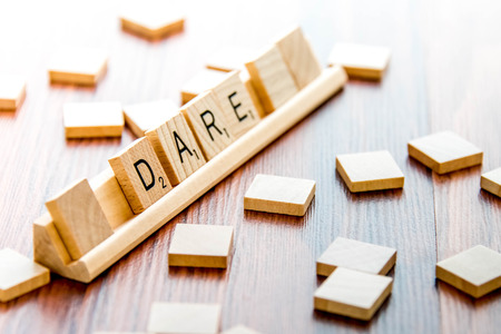 word game: April 4, 2015:  Houston, TX, USA - Scrabble Word Game wood tiles spelling Dare