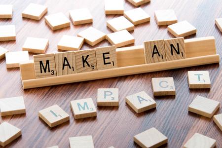 4 april 2015: Houston, TX, USA - Scrabble Word Game houten tegels spelling MAAK EEN IMPACT Redactioneel