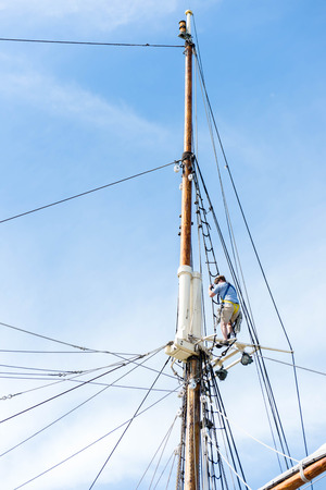 masts: masts, rigging and rolled up sails of a tall sailboat Editorial
