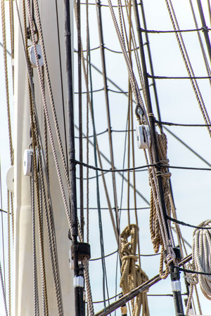 masts, rigging and rolled up sails of a tall sailboat Stok Fotoğraf
