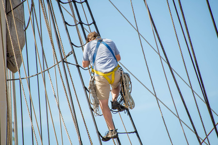 rope ladder: Galveston, TX, USA - October 31, 2014 - man climbing a rope ladder on a sailboat Stock Photo