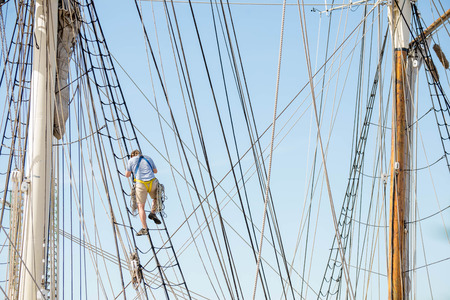 rope ladder: man climbing a rope ladder on a sailboat Stock Photo