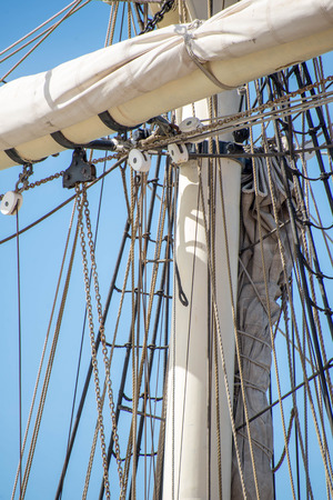 masts: masts, rigging and rolled up sails of a tall sailboat Stock Photo