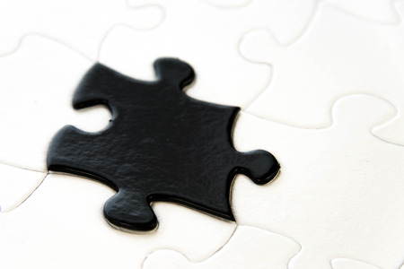 misfit: black and white puzzle pieces contrasting