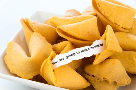 mistakes: open fortune cookie with strip of white paper - YOU ARE GOING TO MAKE MISTAKES