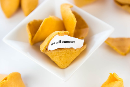 conquer: open fortune cookie with strip of white paper - YOU WILL CONQUER
