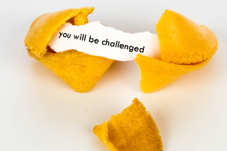 challenged: open fortune cookie with strip of white paper - YOU WILL BE CHALLENGED Stock Photo