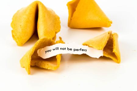백지의 스트립으로 포춘 쿠키를 열어 라. - 너는 완벽하지 않을거야. 스톡 콘텐츠