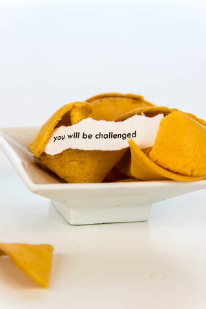bad fortune: open fortune cookie with strip of white paper - YOU WILL BE CHALLENGED Stock Photo