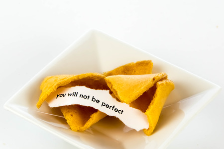 bad fortune: open fortune cookie with strip of white paper - YOU WILL NOT BE PERFECT