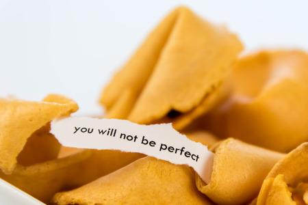 geopend fortune cookie met een strook wit papier - u zult niet perfect
