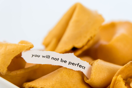 to be or not be: open fortune cookie with strip of white paper - YOU WILL NOT BE PERFECT