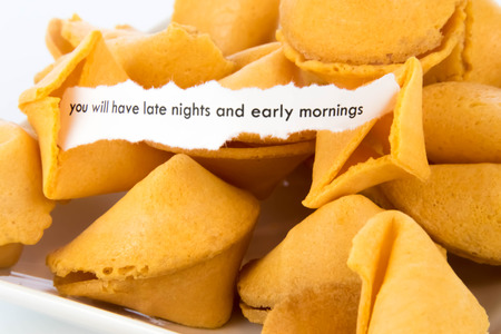 mornings: open fortune cookie with strip of white paper - YOU WILL HAVE LATE NIGHTS AND EARLY MORNINGS