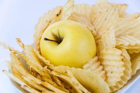 comida chatarra: manzana amarilla vs amarillo papas fritas saladas - decisión merienda entre la alimentación sana o comida chatarra