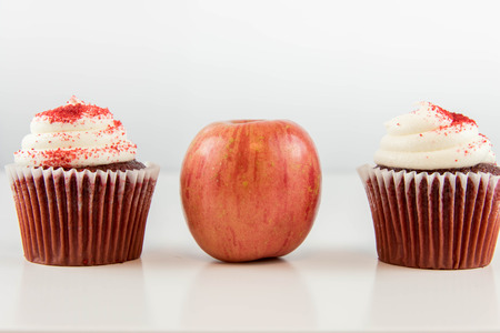 red apple vs red velvet cupcake - snack decision between healthy food or junk food Stock Photo