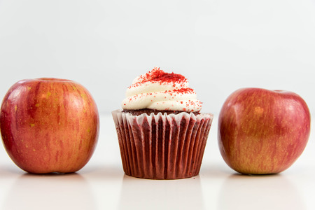 junk: red apple vs red velvet cupcake - snack decision between healthy food or junk food Stock Photo