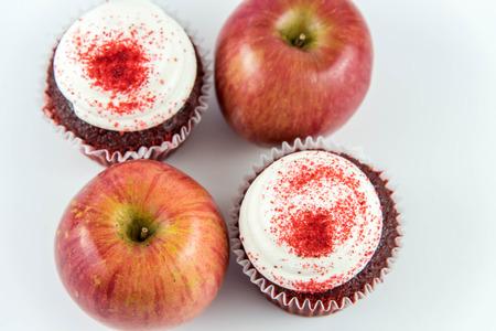 red apple vs red velvet cupcake - snack decision between healthy food or junk food Foto de archivo