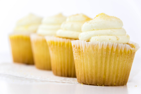 frosting': yellow lemon cupcakes with white frosting Stock Photo