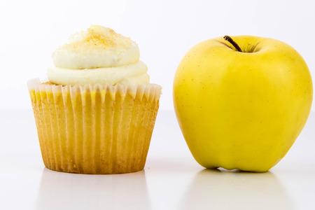 junk: yellow apple vs yellow cupcake - snack decision between healthy food or junk food Stock Photo