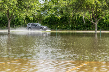 Car in flood waters covering fields and trails