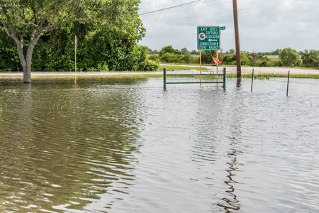 Standing flood waters covering fields and trails