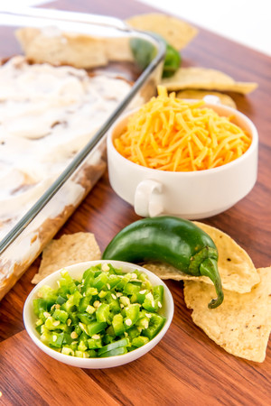 cheddar: preparation of layered bean dip with jalapenos, sour cream and cheddar cheese