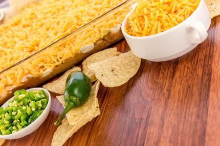 ハラペーニョ、サワー クリームとチェダー チーズの層状豆のディップの準備
