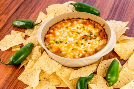 hot layered bean dip with jalapenos, sour cream and melted cheddar cheese