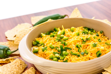preparation of layered bean dip with jalapenos, sour cream and cheddar cheese