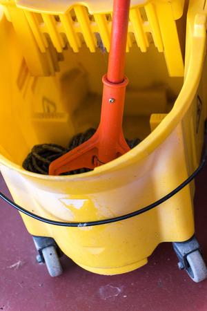 a wet mop in a dry mop bucket Imagens