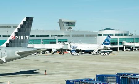 Aviones en la rampa en el aeropuerto de San Antonio con la torre de control en el fondo