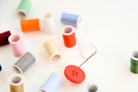 針の目を通して赤い糸と多色の糸スプールが付いている赤いボタン
