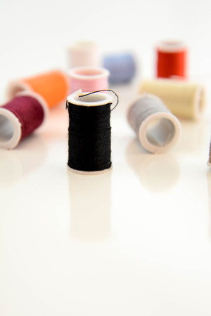 Red thread through needle eye and red button with multi colored thread spools Stock Photo
